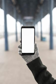 Primer plano de la mano con guantes que muestran un teléfono inteligente con pantalla blanca