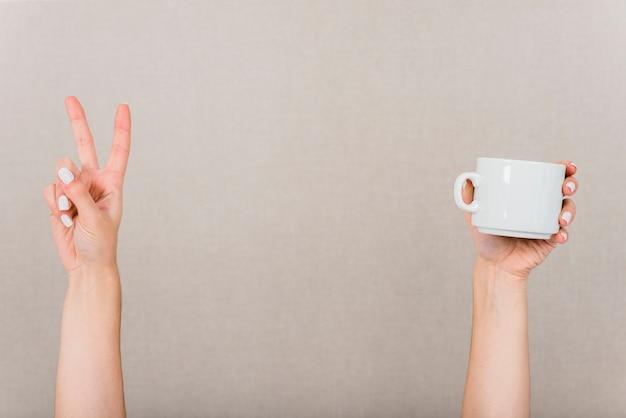 Primer plano de la mano haciendo un gesto de paz y una taza blanca sobre fondo coloreado
