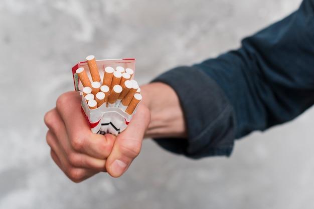 Primer plano de la mano del hombre aplastando caja de cigarrillos