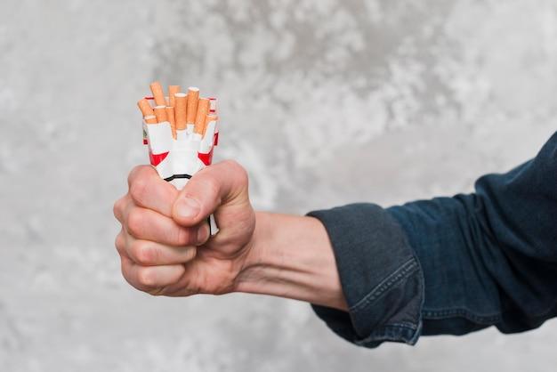 Primer plano de la mano del hombre aplastando paquete de cigarrillo