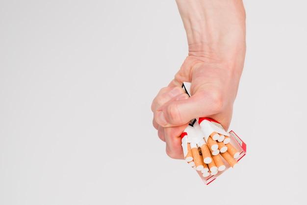 Primer plano de la mano del hombre aplastando un paquete de cigarrillos