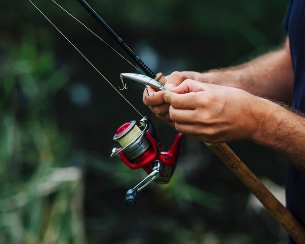 Primer plano de la mano del hombre atar anzuelo de pesca