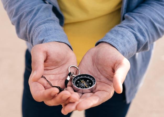 Primer plano de la mano del hombre con brújula de navegación