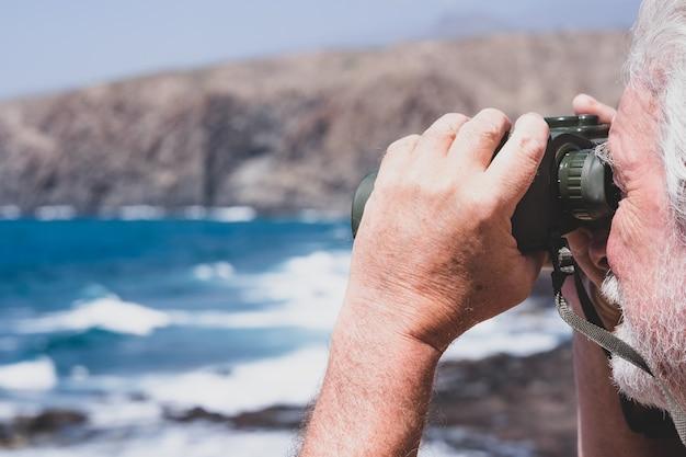 Primer plano de la mano del hombre caucásico sosteniendo binoculares mirando al mar, montaña. senior jubilado disfrutando de la libertad y el conocimiento