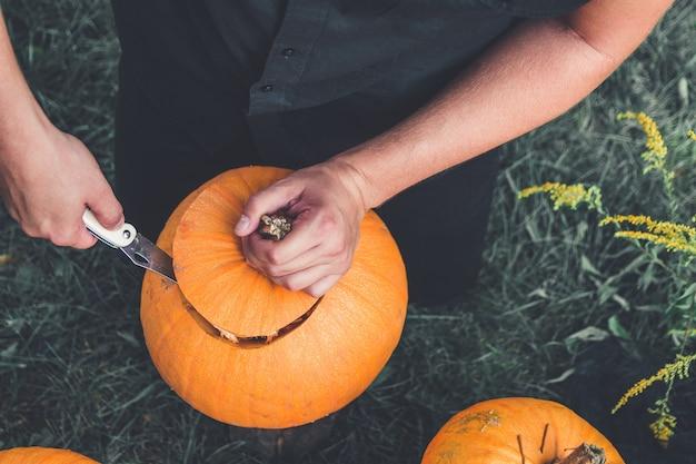 Un primer plano de la mano del hombre corta la tapa de una calabaza mientras prepara una jack-o-lantern. víspera de todos los santos. decoración para fiesta. vista superior. foto tonificada.