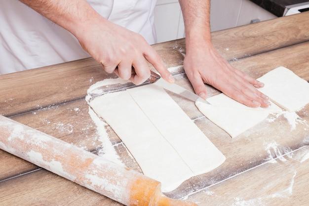 Primer plano de la mano del hombre cortando la masa enrollada con un cuchillo en la mesa