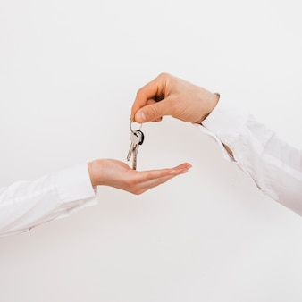 Primer plano de una mano de hombre dando llaves a mujer
