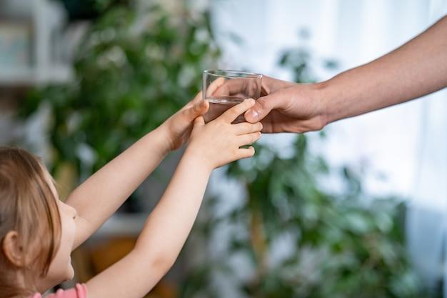 Primer plano de la mano de un hombre dando un vaso de agua fresca filtrada a un niño.