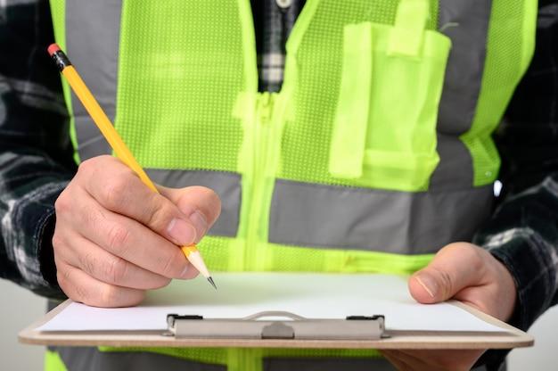 Un primer plano de la mano de un hombre firmando un documento con un portapapeles.