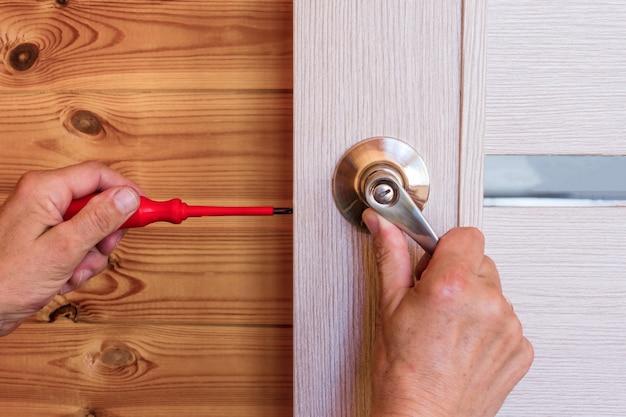 Primer plano de la mano del hombre instalar la cerradura de la puerta en casa.