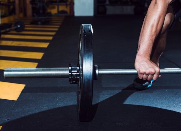 Primer plano de la mano de un hombre levantando pesas
