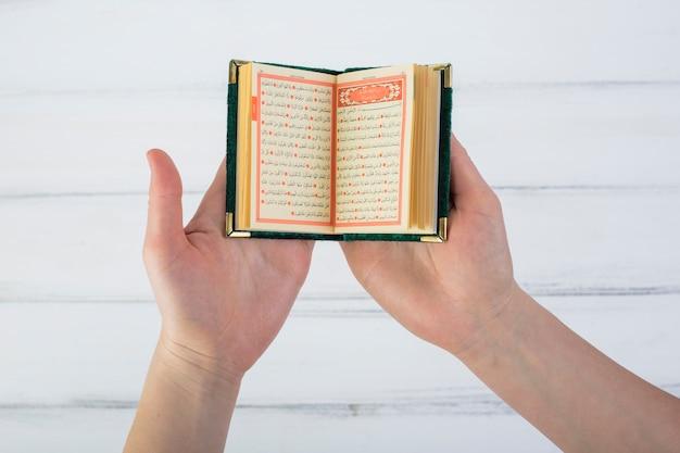 Primer plano de la mano de un hombre leyendo el corán sobre la mesa de madera blanca