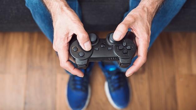 Primer plano de la mano del hombre mayor que sostiene la consola de videojuegos