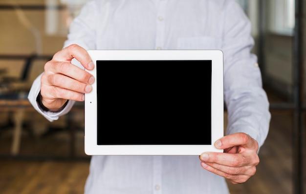 Primer plano de la mano del hombre mostrando tableta digital