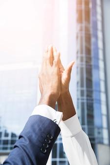 Primer plano de la mano del hombre de negocios y de la empresaria que da el alto cinco