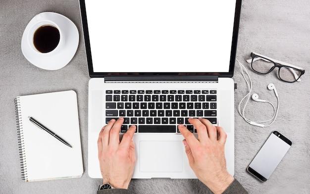 Primer plano de la mano de un hombre de negocios escribiendo en tableta digital con suministros de oficina y taza de café en el escritorio