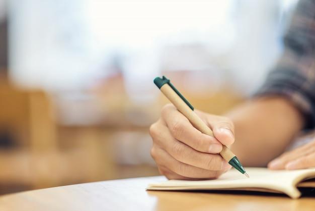 Primer plano de la mano del hombre de negocios con la escritura de la pluma en el cuaderno