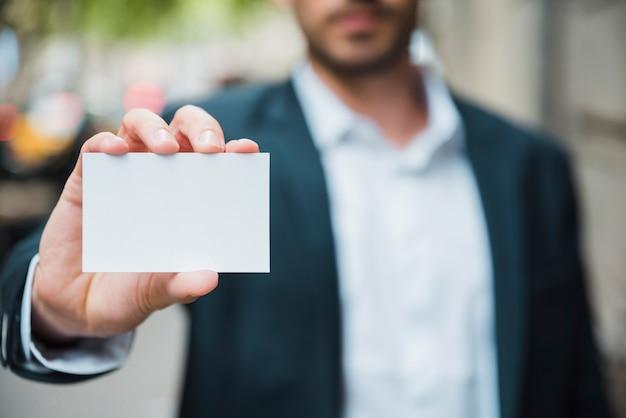 Primer plano de la mano del hombre de negocios que muestra la tarjeta de visita blanca