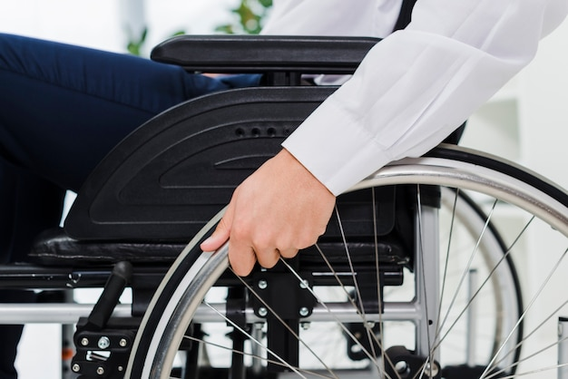 Primer plano de la mano de un hombre de negocios sobre una rueda de silla de ruedas