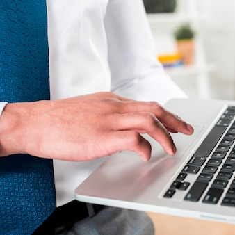 Primer plano de la mano de un hombre de negocios usando laptop