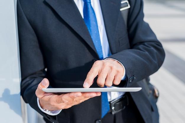 Primer plano de la mano de un hombre de negocios usando tableta digital