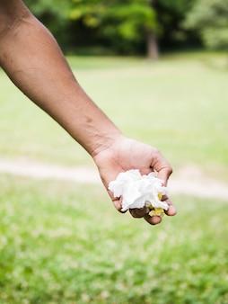 Primer plano de la mano del hombre con papel arrugado en el parque