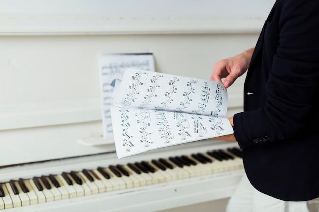 Primer plano de la mano del hombre pasando la página de la hoja musical.