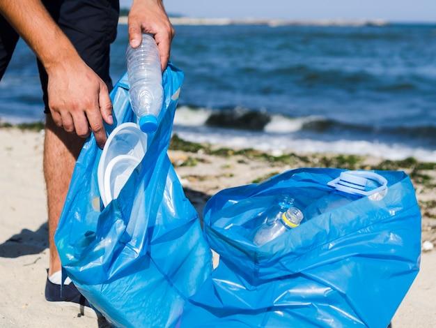 Primer plano de la mano del hombre poniendo una botella de plástico vacía en una bolsa de basura azul en la playa