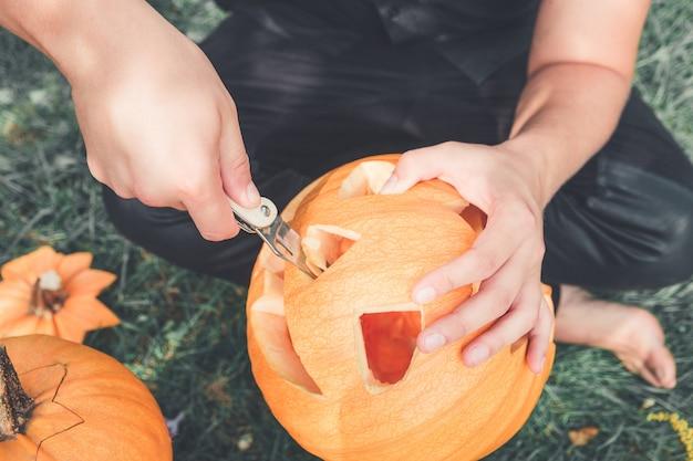 Un primer plano de la mano del hombre que corta con un cuchillo una calabaza mientras prepara una jack-o-lantern. víspera de todos los santos. decoración para fiesta. foto tonificada.