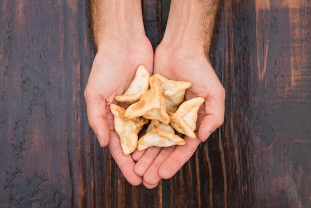 Primer plano de la mano de un hombre que muestra bolas de masa hervida contra el fondo de textura de madera