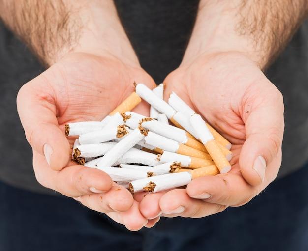Primer plano de la mano de un hombre que muestra cigarrillos rotos