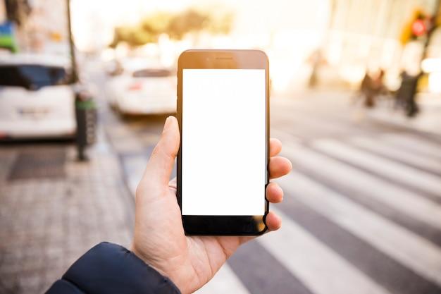 Primer plano de la mano del hombre que muestra el teléfono móvil con pantalla en blanco en la carretera