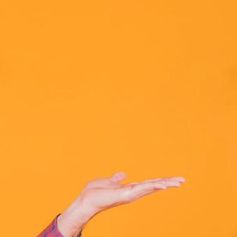 Primer plano de la mano del hombre que presenta algo contra un fondo naranja