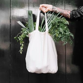 Primer plano de la mano del hombre que sostiene la bolsa de la compra blanca llena de verduras de hoja