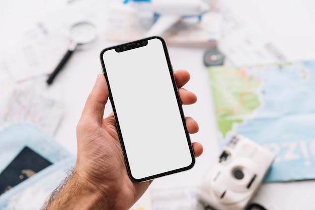 Primer plano de la mano del hombre que sostiene el móvil con pantalla blanca contra el fondo borroso