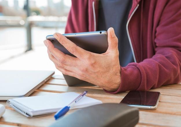 Primer plano de la mano del hombre que sostiene la tableta digital en la mano en un café al aire libre