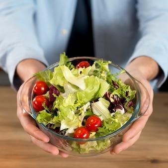 Primer plano de la mano de un hombre que sostiene un tazón de ensalada fresco sobre el escritorio de madera