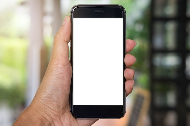 Primer plano de una mano del hombre que sostiene el teléfono elegante con la pantalla en blanco móvil en cafetería.