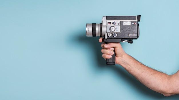 Primer plano de la mano del hombre que sostiene la videocámara pasada de moda contra el fondo azul