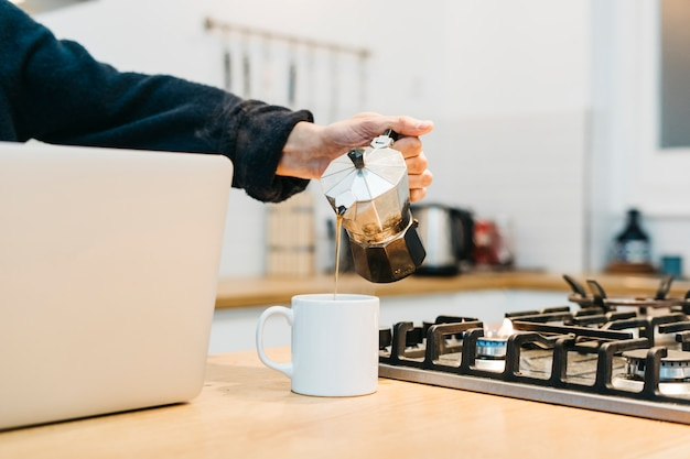 Primer plano de la mano de un hombre que vierte el café en una taza blanca cerca de la encimera de gas