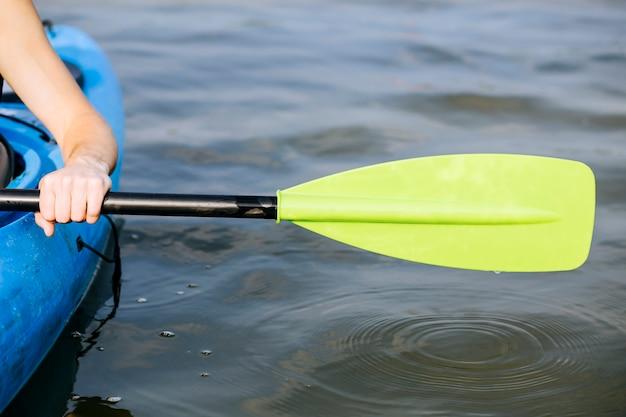 Primer plano de la mano de un hombre remando un kayak
