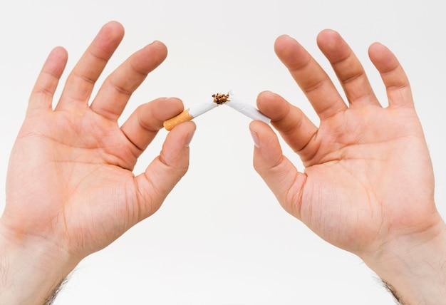 Primer plano de la mano de un hombre rompiendo el cigarrillo contra el fondo blanco