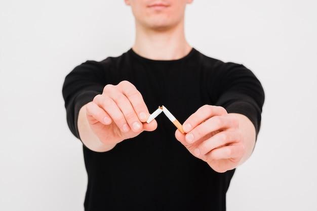 Primer plano de la mano del hombre rompiendo cigarrillos