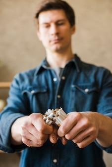 Primer plano de la mano del hombre roto paquete de cigarrillos