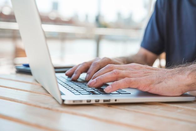 Primer plano de la mano del hombre senior escribiendo en la computadora portátil