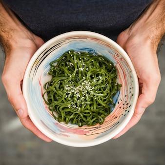Primer plano de la mano de un hombre sosteniendo un tazón de algas con semillas de sésamo
