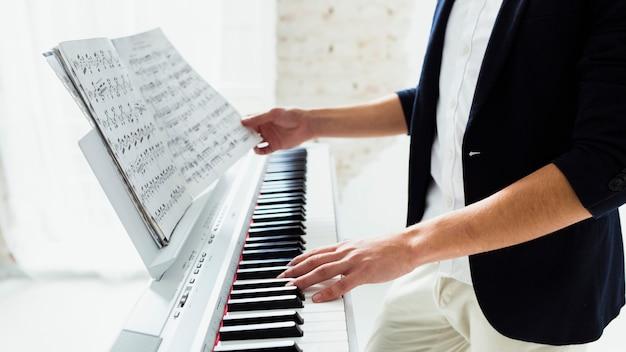 Primer plano de la mano del hombre tocando el piano