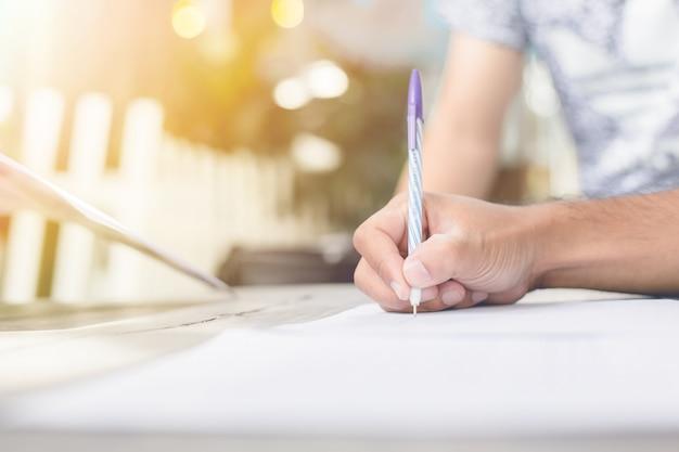 Primer plano de una mano humana escribiendo algo en el papel, luz de la mañana