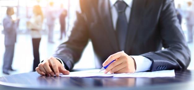 Primer plano de la mano humana escribiendo en el papel sobre el trabajo del equipo