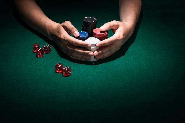 Primer plano de una mano humana con pila de fichas de casino
